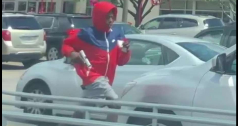 Armed man running away in a red hoodie to a robbery.